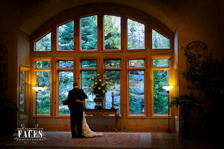 Bride and groom hugging in front of window with beautiful scenery