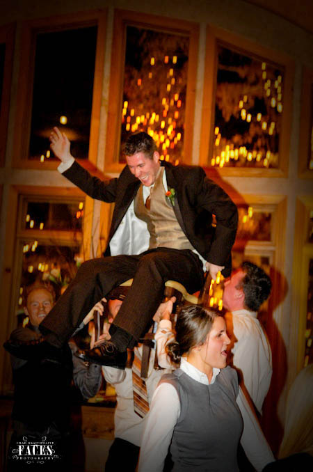 Groom being lifted up into the air on a chair