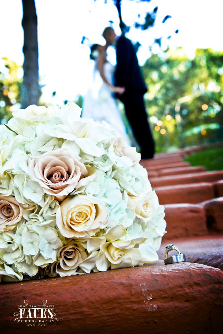 Bouquet and rings with groom and bride kissing in the background