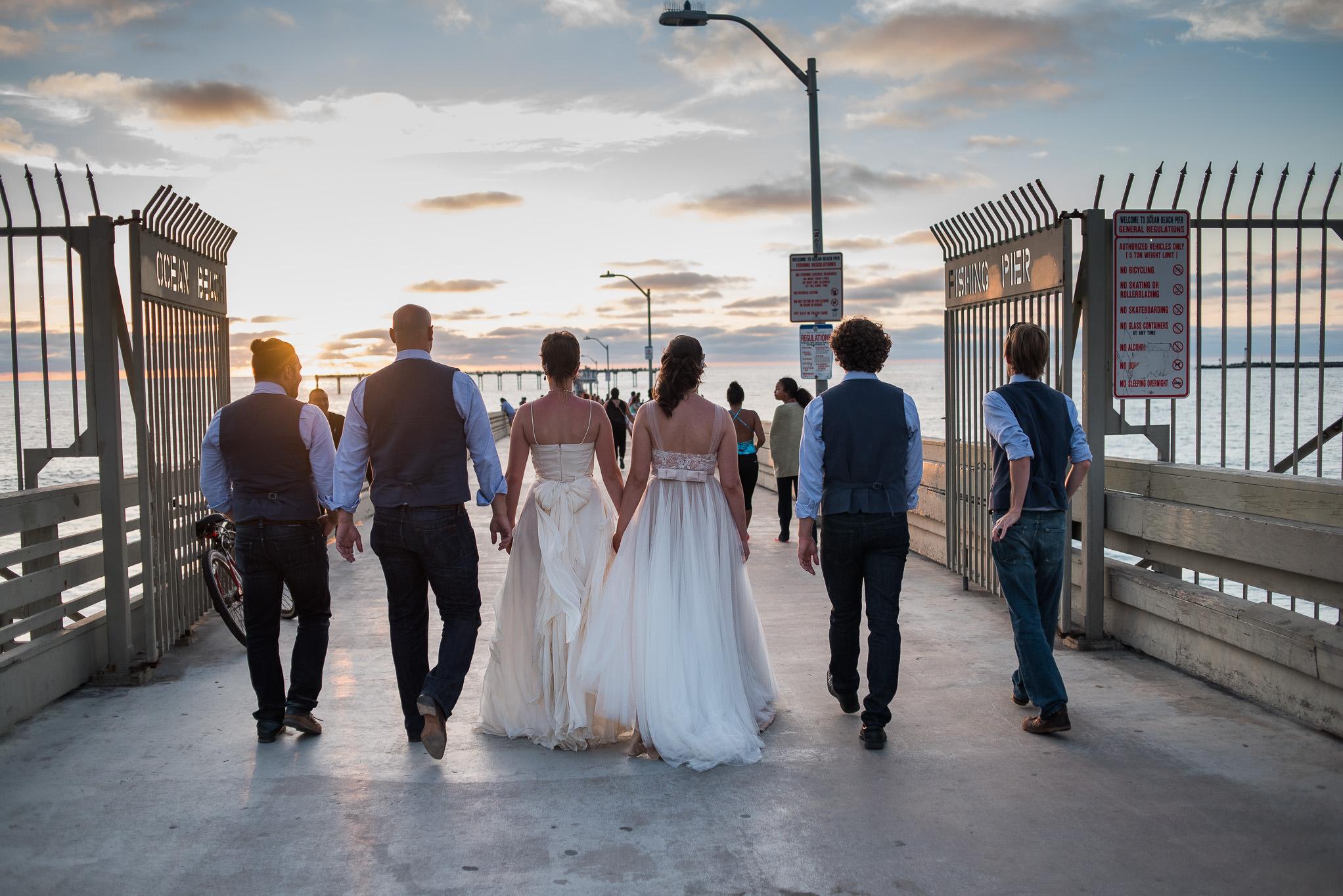 Two brides in Sand Diego walking pier with groomsmen