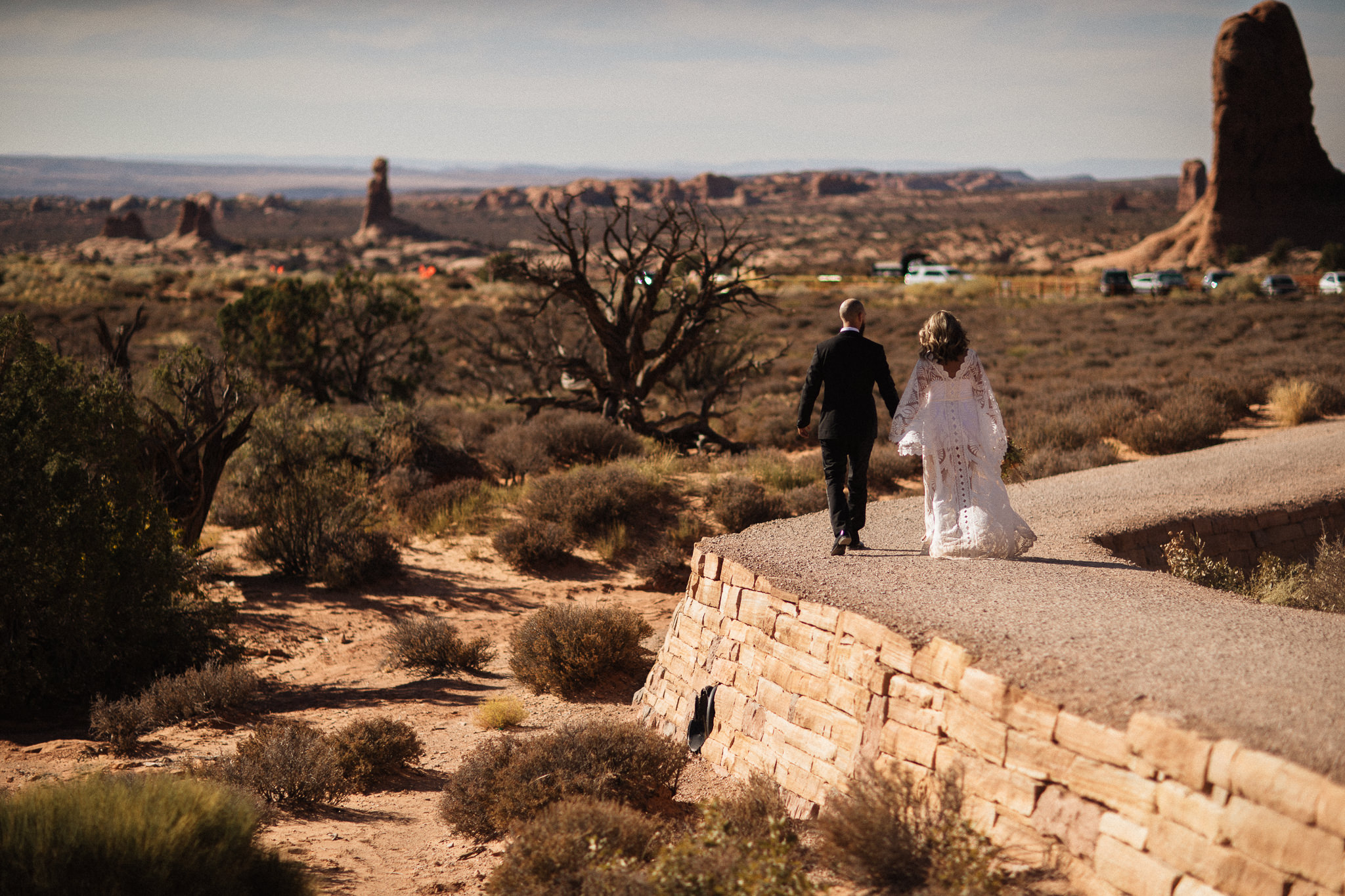 Bride and Groom walking to see double arch